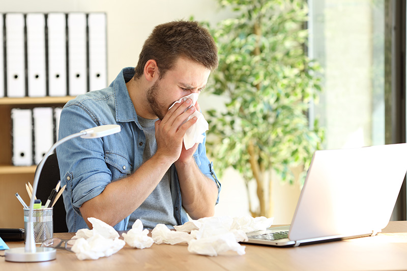 Sick employee blowing his nose while sitting in front of his laptop